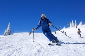 woman skiing on ski slope with blue sky